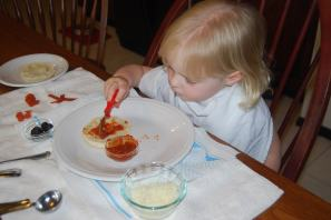 Two-year-old granddaughter making English muffin happy face pizzas